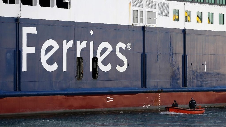 A small vessel carring two workers pass by a docked ferry at the port of Piraeus, near Athens, Friday, Dec. 2, 2016. Ferries across Greece are to remain tied up in port for two days as seamen walk off the job to protest proposed tax hikes. (AP Photo/Thanassis Stavrakis)