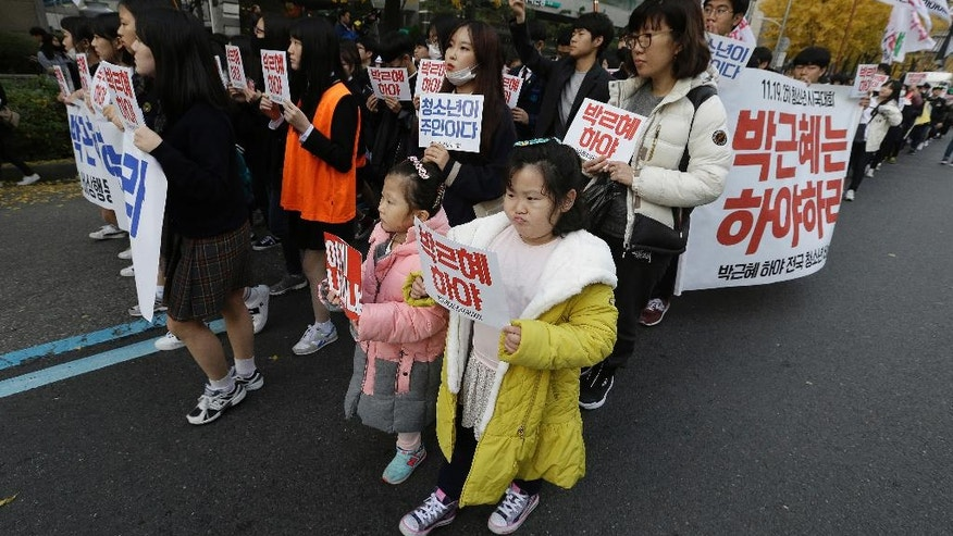 FILE - In this Saturday, Nov. 19, 2016, file photo, South Korean children march with high school students during a rally calling for South Korean President Park Geun-hye to step down in Seoul, South Korea.  There's more Disney than street-fighting at protests meant to force President Park from power over corruption allegations. Yet they share an important quality with past violent rallies: Now, as then, a huge popular movement is on the verge of pushing out a deeply unpopular leader. (AP Photo/Ahn Young-joon, File)