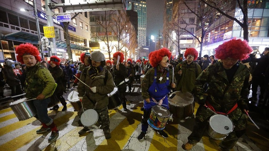 FILE - In this Saturday, Nov. 26, 2016, file photo, South Korean protesters beat their drums as they march during a rally calling for South Korean President Park Geun-hye to step down in Seoul, South Korea. There's more Disney than street-fighting at protests meant to force President Park from power over corruption allegations. Yet they share an important quality with past violent rallies: Now, as then, a huge popular movement is on the verge of pushing out a deeply unpopular leader. (AP Photo/Ahn Young-joon, File)