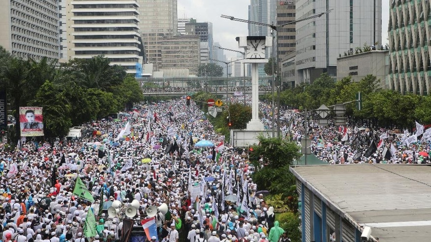 """Indonesian Muslims march during a rally against Jakarta's minority Christian Governor Basuki """"Ahok"""" Tjahaja Purnama who is being prosecuted for blasphemy, at the National Monument in Jakarta, Indonesia, Friday, Dec. 2, 2016. Several hundred thousands of conservative Muslims rallied in the Indonesian capital on Friday in the second major protest in a month against the minority Christian governor. (AP Photo/Tatan Syuflana)"""