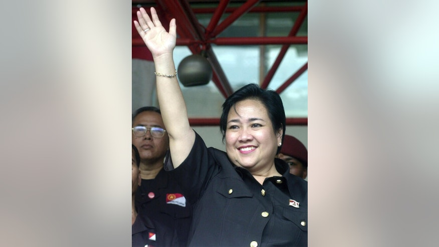 FILE - In this Thursday, April 1, 2004, file photo, Rachmawati Sukarnoputri, the leader of the Pioneer Party and sister of former Indonesian President Megawati Sukarnoputri, waves to supporters during a campaign rally in Jakarta, Indonesia. Indonesian police arrested 10 people including Rachmawati for suspected treason and other crimes and said they were planning to use a mass protest in the capital on Friday to cause chaos and overthrow the government. (AP Photo/Achmad Ibrahim, File)