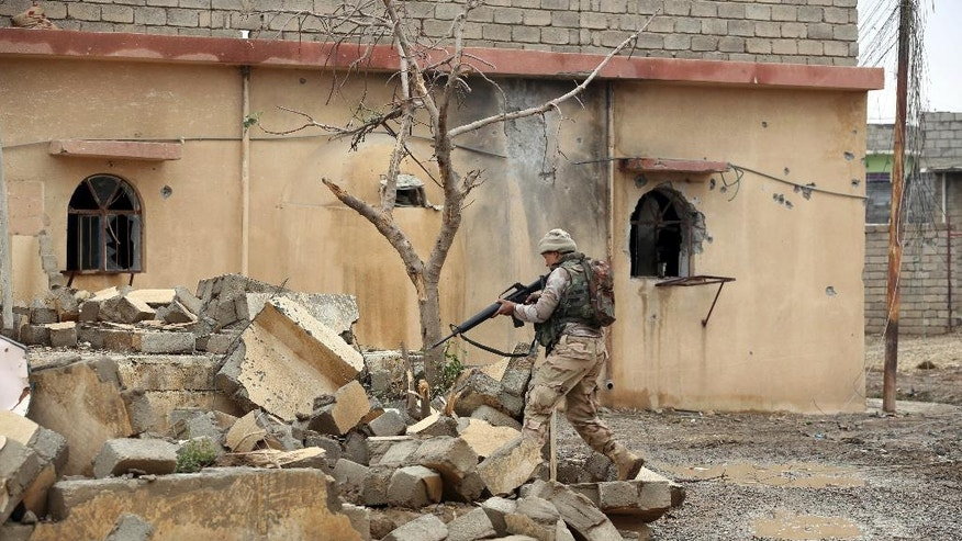 An Iraqi Army soldier searches for Islamic State militants in a recently liberated village outside Mosul, Iraq, Thursday, Dec. 1, 2016. (AP Photo/Hadi Mizban)