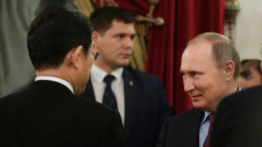 Russian President Vladimir Putin, right, meets with Japanese Foreign Minister Fumio Kishida, left, in St. Petersburg, Russia, Friday, Dec. 2, 2016. Putin is to travel to Japan later this month to meet the Japanese prime minister and discuss a territorial dispute over the southern Kuril islands which keeps the two countries from signing a peace treaty formally ending their World War II hostilities. (AP Photo/Dmitri Lovetsky, pool)