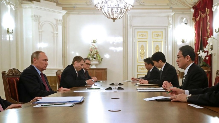 Russian President Vladimir Putin, left, meets with Japanese Foreign Minister Fumio Kishida, right, in St. Petersburg, Russia, Friday, Dec. 2, 2016. Putin is to travel to Japan later this month to meet the Japanese prime minister and discuss a territorial dispute over the southern Kuril islands which keeps the two countries from signing a peace treaty formally ending their World War II hostilities. (AP Photo/Dmitri Lovetsky, pool)