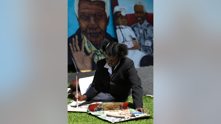 Angel Sirenje, a 12 years old girl, draws a portrait of the late former South African president Nelson Mandela during the official opening of the Nelson Mandela Children's Hospital in Johannesburg, South Africa, Friday, Dec. 2, 2016. The 200-bed Nelson Mandela Children's Hospital, conceived by Mandela more than a decade ago, will employ 150 pediatric doctors and 450 nurses. (AP Photo/Themba Hadebe)