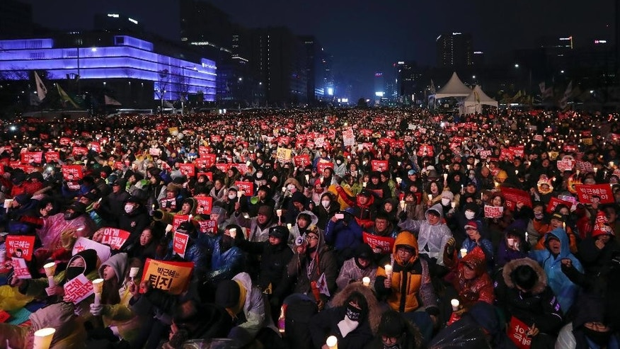 In this photo taken on Saturday, Nov. 26, 2016, South Korean protesters hold up candles during a rally calling for South Korean President Park Geun-hye to step down in Seoul, South Korea. South Korea's main opposition parties said Friday they will push for a vote next week on President Park Geun-hye's impeachment. (AP Photo/Lee Jin-man)