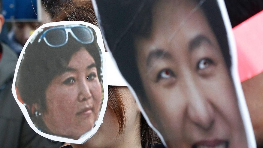 FILE - In this Wednesday, Nov. 2, 2016, file photo, South Korean protesters wearing masks of South Korean President Park Geun-hye, right, and her confidante Choi Soon-sil, who is at the center of a political scandal, attend a rally calling for Park to step down in downtown Seoul. There's more Disney than street-fighting at protests meant to force President Park from power over corruption allegations. Yet they share an important quality with past violent rallies: Now, as then, a huge popular movement is on the verge of pushing out a deeply unpopular leader. (AP Photo/Ahn Young-joon, File)