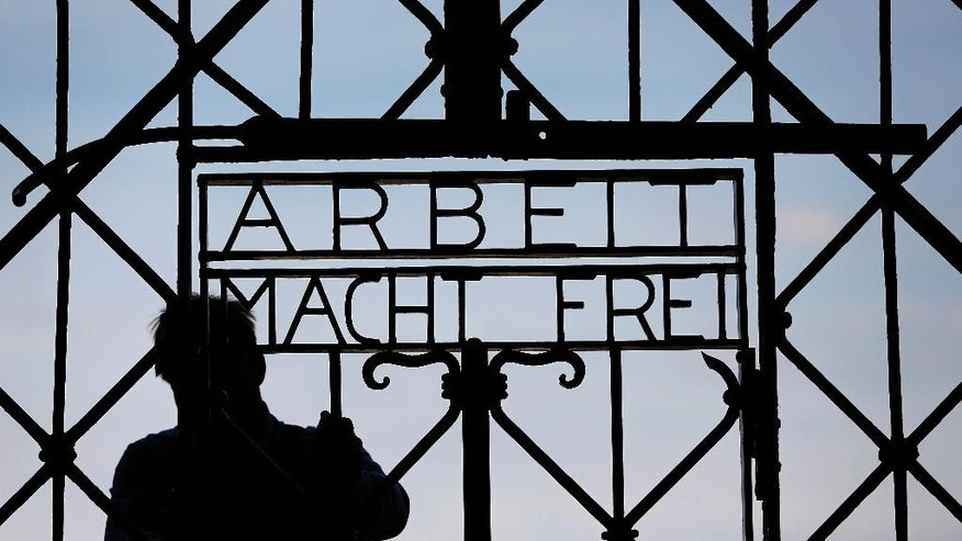 "FILE In this April 29, 2015 file picture a  blacksmith prepares a replica of the Dachau Nazi concentration camp gate, with the writing ""Arbeit macht frei"" (Work Sets you Free) at the main entrance of the memorial in Dachau, Germany,. German police say Friday Dec. 2, 2016 the wrought-iron gate to the Nazis' Dachau concentration camp that was stolen two years ago appears to have been found in western Norway.  (AP Photo/Matthias Schrader,File)"