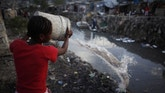 A resident throws dirty water into a drain which leads into the sea in Port-au-Prince October 29, 2010. The unusually high death rate in Haiti's cholera epidemic is slowing as people become aware of the disease and health experts provide treatment, the World Health Organisation said on Wednesday. The United Nations agency's key aim now is to prevent the disease from spreading south to the capital Port-au-Prince and the camps for homeless survivors of the Jan. 12 earthquake, from the northern department of Artibonite where it is concentrated.