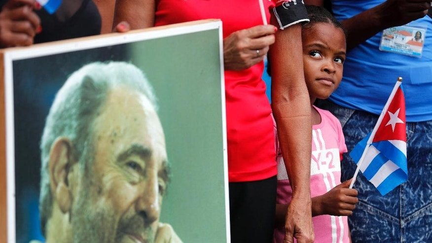 A child stands next to a portrait of the late Cuban leader Fidel Castro as she waits for the arrival of the motorcade carrying the ashes of Castro at the Cespedes park in Santiago, Cuba, Saturday, Dec. 3, 2016. After days of national mourning in Cuba and a tour of his ashes through the countryside, his remains have arrived to the city where they will be laid to rest.(AP Photo/Dario Lopez-Mills)