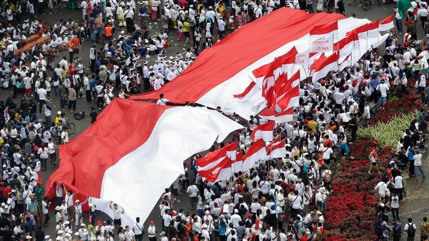 Indonesians display a large red and white national flag and smaller ones during a rally in Jakarta, Indonesia, Sunday, Dec. 4, 2016. Thousands of people staged the rally in attempt to demonstrate national unity as religious and racial tensions divide the world's most populous Muslim nation. (AP Photo/Achmad Ibrahim)