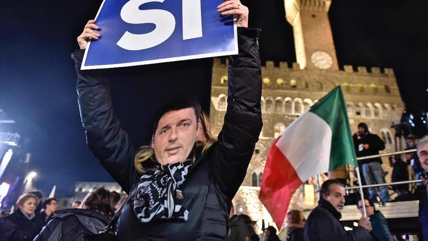 "A woman wears a mask of Italian Premier Matteo Renzi as she holds up a sign reading ""Yes"" during a rally on the upcoming Italian constitutional referendum in Florence, Italy, Friday, Dec. 2, 2016. (Maurizio Degl'Innocenti/ANSA via AP)"