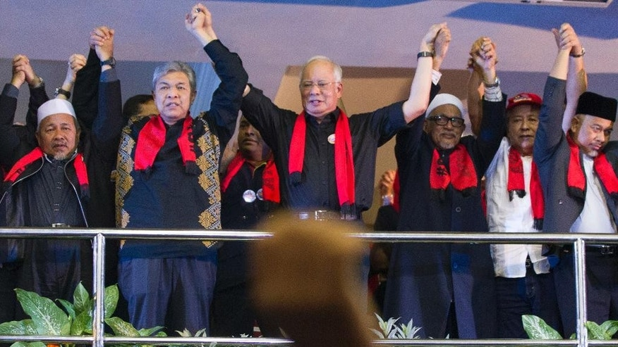 Malaysian Prime Minister Najib Razak, center, holds hands with other leaders during a protest against the persecution of Rohingya Muslims in Myanmar, at a stadium in Kuala Lumpur, Malaysia, Sunday, Dec. 4, 2016. Najib led a protest rally Sunday against what he called a genocide of Myanmar's Muslim Rohingya minority and urged the international community to help halt the atrocities. (AP Photo/Lim Huey Teng)