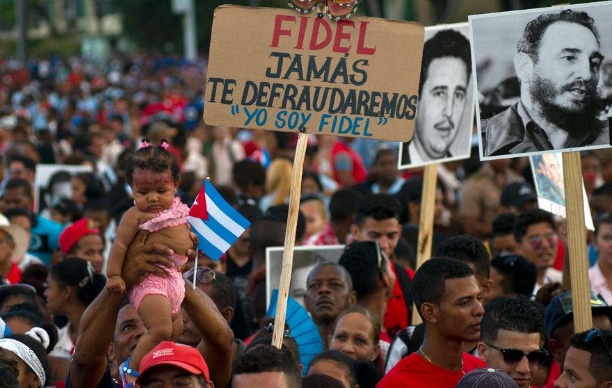 People waits for the beginning of a rally honoring Cuba's leader Fidel Castro before his burial Sunday at the Plaza Antonio Maceo in Santiago, Cuba, Saturday, Dec. 3, 2016. The sign reads in Spanish 'Fidel we will never let you down. I am Fidel.'(AP Photo/Ramon Espinosa)