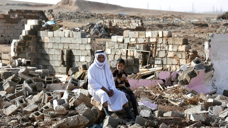 Arab residents sit amid their destroyed home in Kirkuk's Huzeiran neighborhood, Iraq, Friday, Dec. 2, 2016. In the weeks following a deadly Islamic State group attack in central Kirkuk, residents of the city's Arab neighborhoods say Kurdish security forces moved into a small mostly Arab neighborhood on the city's southern edge, destroyed homes and confiscated identity documents. (AP Photo/Hadi Mizban)