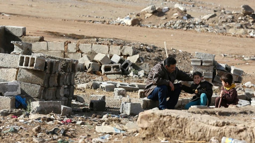 An Arab man and his children sit amid the rubble of their destroyed home in Kirkuk's Huzeiran neighborhood, Iraq, Friday, Dec. 2, 2016. In the weeks following a deadly Islamic State group attack in central Kirkuk, residents of the city's Arab neighborhoods say Kurdish security forces moved into a small mostly Arab neighborhood on the city's southern edge, destroyed homes and confiscated identity documents. (AP Photo/Hadi Mizban)