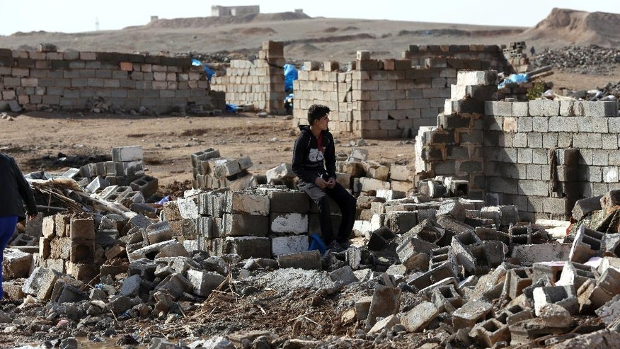 An Arab man sits on the rubble of his destroyed home in Kirkuk's Huzeiran neighborhood, Iraq, Friday, Dec. 2, 2016. In the weeks following a deadly Islamic State group attack in central Kirkuk, residents of the city's Arab neighborhoods say Kurdish security forces moved into a small mostly Arab neighborhood on the city's southern edge, destroyed homes and confiscated identity documents. (AP Photo/Hadi Mizban)