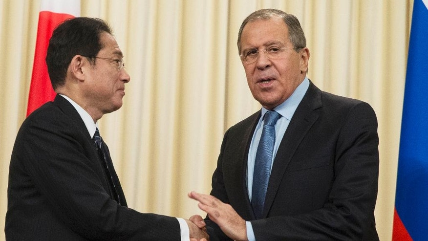 Russian Foreign Minister Sergey Lavrov, right, and Japanese Foreign Minister Fumio Kishida, shake hands after a news conference in Moscow, Russia, Saturday, Dec. 3, 2016. Russian President Vladimir Putin is going to travel to Japan later this month to meet the Japanese prime minister and discuss a territorial dispute over the southern Kuril islands which keeps the two countries from signing a peace treaty formally ending their World War II hostilities. (AP Photo/Pavel Golovkin)
