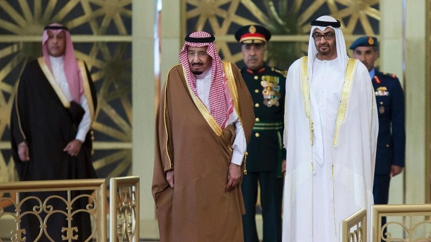 In this Saturday Dec. 3, 2016 photo released by Emirates News Agency, WAM, Sheikh Mohamed bin Zayed Al Nahyan, Crown Prince of Abu Dhabi and Deputy Supreme Commander of the UAE Armed Forces, right, receives Saudi King Salman in Abu Dhabi, United Arab Emirates. King Salman has arrived in the United Arab Emirates to begin a regional tour aimed at strengthening relations with four neighboring Gulf allies. (Emirates News Agency via AP)