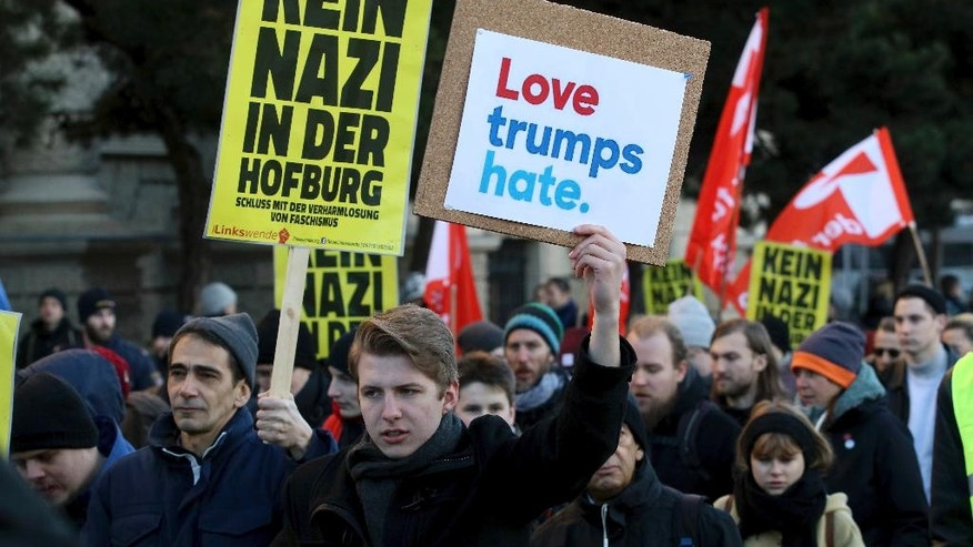 Protesters walk during a demonstration against Norbert Hofer, candidate for presidential elections of Austria's right-wing Freedom Party, FPOE, in Vienna, Austria, Saturday, Dec. 3, 2016. The poster on the left reads 'No Nazis in the Hofburg' referring to Austria's presidential palace.  (AP Photo/Ronald Zak)