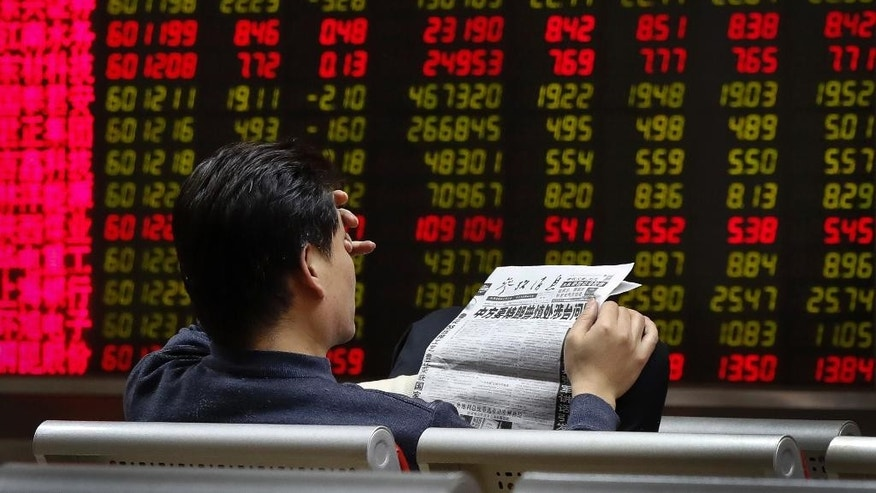"A man reads a newspaper with the headline that reads ""China want U.S. President-elect Donald Trump use caution in dealing with Taiwan issue"" at a brokerage house in Beijing, Monday, Dec. 5, 2016. With Trump's latest tweets touching on highly sensitive issues, China must decide how to handle an incoming American president who relishes confrontation and whose online statements appear to foreshadow shifts in foreign policy. (AP Photo/Andy Wong)"