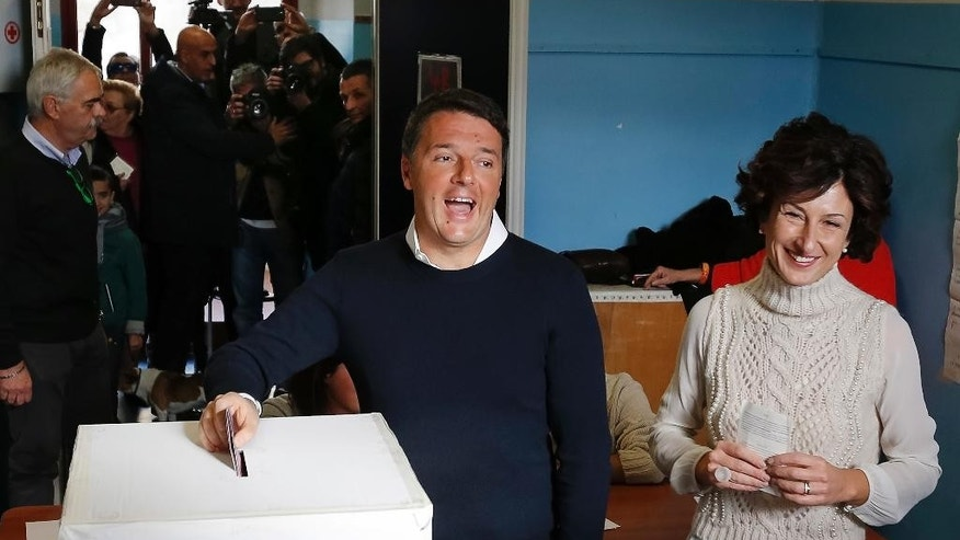Italian Premier Matteo Renzi is flanked by his wife Agnese as he casts his ballot at a polling station in Pontassieve, Italy, Sunday, Dec. 4, 2016. Italians are voting in a referendum on constitutional reforms that is being closely watched abroad to see if Italy is the next country to reject the political status quo. Premier Matteo Renzi has said he would resign if the reforms are rejected in Sunday's vote, and opposition politicians have vowed to press for a new government if voters reject the proposed constitutional changes. (AP Photo/Antonio Calanni)
