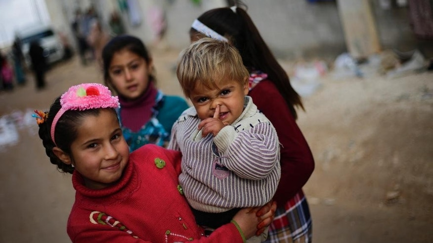 Syrian children displaced with their families from eastern Aleppo pose for a picture in the village of Jibreen south of Aleppo, Syria, Saturday, Dec. 3, 2016. Aid agencies say that more than 30,000 people have fled rebel-held eastern neighborhoods of Aleppo that have been under tight siege since July. Over the past two weeks, government forces launched an offensive in which they regained control of nearly half areas that had been held by insurgents in their deepest push since the city became contested in July 2012.(AP Photo/Hassan Ammar)