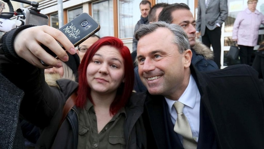 Norbert Hofer of Austria's Freedom Party, FPOE, takes pictures with a girl after casting his vote during the Austrian presidential elections, in Pinkafeld, Austria, Sunday, Dec. 4, 2016. (AP Photo/Ronald Zak)