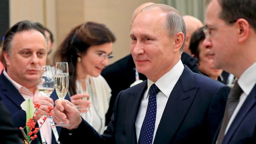 In this photo taken Friday, Dec. 2, 2016 Russian President Vladimir Putin toasts at a meeting with Russian and foreign cultural figures in the Mariinsky Theater in St. Petersburg, Russia. At right, Russian Culture Minister Vladimir Medinsky. At left back, Russia's Vakhtangov theater director Kirill Krok. (Mikhail Klimentyev/Sputnik, Kremlin Pool Photo via AP)
