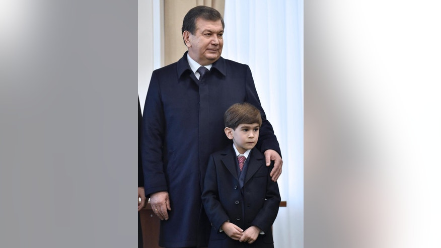 Uzbek acting President Shavkat Mirziyoyev and his grandson, poses for the media during the presidential election in Tashkent, Uzbekistan on Sunday, Dec. 4, 2016. Mirziyoyev, who spent 13 years as Karimov's prime minister, is expected to easily win a five-year term. Karimov led Uzbekistan since before the Soviet collapse, first as its communist boss and then as president. (AP Photo/Anvar Ilyasov, Pool)