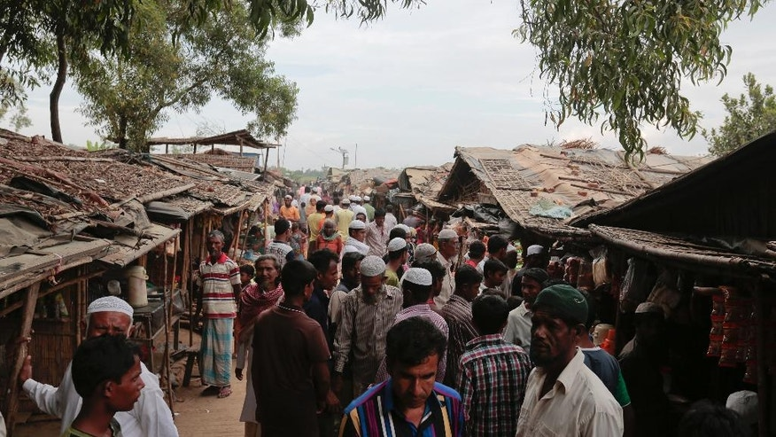 In this Dec. 2, 2016 photo, Rohingya from Myanmar make their way in an alley at an unregistered refugee camp in Teknaf, near Cox's Bazar, a southern coastal district about, 296 kilometers (183 miles) south of Dhaka, Bangladesh. Some 15,000 Rohingya have arrived in Bangladesh over past month, often brought in by smugglers, according to police and intelligence officials, speaking on condition of anonymity. They have joined up to 500,000 undocumented Rohingya who have been living in Bangladesh after arriving from Myanmar in waves since the 1970s. In refugee camps in Bangladesh, survivors of a wave of violence that has swept Myanmar in recent weeks say government forces have targeted minority Rohingya villages, burning many to the ground, killing the innocent and raping women. (AP Photo/A.M. Ahad)