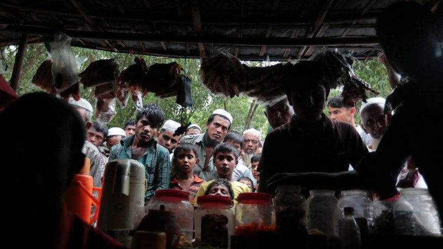 In this Dec. 2, 2016 photo, Rohingya from Myanmar, watch a television program about them being played on a mobile phone inside a tea stall, at an unregistered refugee camp in Teknaf, near Cox's Bazar, a southern coastal district about, 296 kilometers (183 miles) south of Dhaka, Bangladesh. Some 15,000 Rohingya have arrived in Bangladesh over past month, often brought in by smugglers, according to police and intelligence officials, speaking on condition of anonymity. They have joined up to 500,000 undocumented Rohingya who have been living in Bangladesh after arriving from Myanmar in waves since the 1970s. Survivors of a wave of violence that has swept Myanmar in recent weeks say government forces have targeted minority Rohingya villages, burning many to the ground, killing the innocent and raping women. (AP Photo/A.M. Ahad)