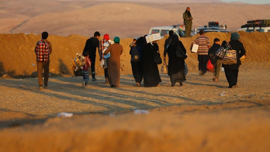 In this photo taken on Friday November 18, 2016, Iraqi citizens fleeing the fighting between Iraqi forces and Islamic State militants, cross to the Kurdish areas through a sand barrier created by Kurdish forces to demarcate their border, at an open field in the Nineveh plain, northeast of Mosul, Iraq. The sand berms and trenches snake across northern Iraq all the way to Syria, alongside newly paved roads and sprawling checkpoints decked with Kurdish flags, in what increasingly resembles an international border. The boundary takes in lands claimed by the Kurds and the Baghdad government, and could ignite a new conflict once the Islamic State group is defeated. (AP Photo/Hussein Malla)
