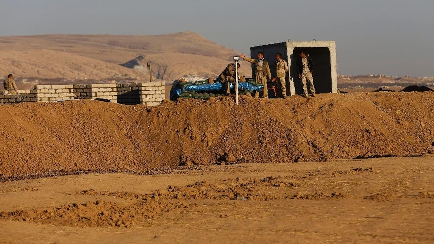 In this photo taken on Friday November 18, 2016, Kurdish Peshmerga fighters stand at one of their positions over a sand barrier created by Kurdish forces to demarcate their border, at an open field in the Nineveh plain, northeast of Mosul, Iraq. The sand berms and trenches snake across northern Iraq all the way to Syria, alongside newly paved roads and sprawling checkpoints decked with Kurdish flags, in what increasingly resembles an international border. The boundary takes in lands claimed by the Kurds and the Baghdad government, and could ignite a new conflict once the Islamic State group is defeated. (AP Photo/Hussein Malla)