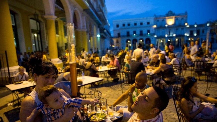 A family enjoys a meal and beer at a square in Havana, Cuba,  Monday, Dec. 5, 2016. Nine days of mourning for Fidel Castro end and Cuba begins to resume its life, with music in the streets, alcohol sold again and work returning to a normal pace. (AP Photo/Enric Marti)