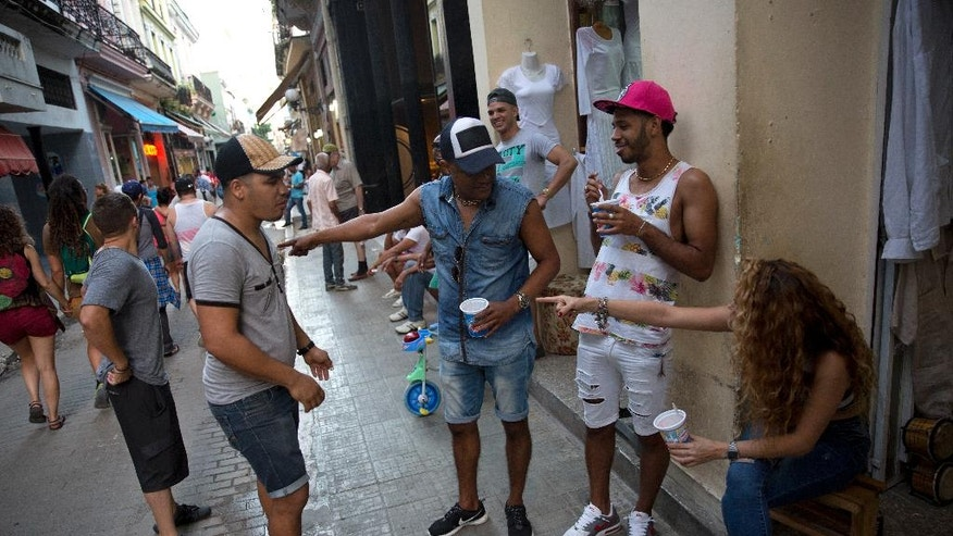 Cubans enjoy an ice-cream at a busy street in central Havana, Cuba,  Monday, Dec. 5, 2016. Nine days of mourning for Fidel Castro end and Cuba begins to resume its life, with music in the streets, alcohol sold again and work returning to a normal pace. (AP Photo/Enric Marti)