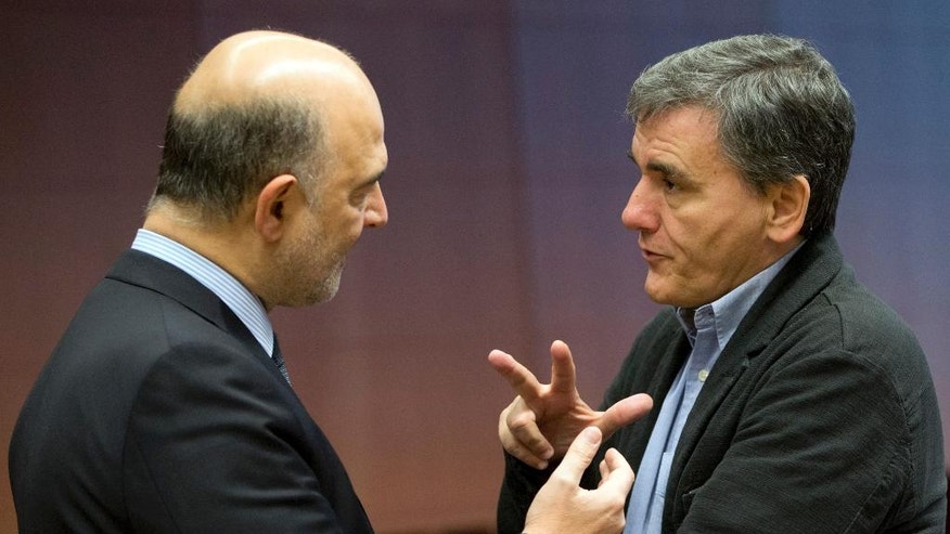Greek Finance Minister Euclid Tsakalotos, right, speaks with European Commissioner for Economic and Financial Affairs Pierre Moscovici during a round table meeting of eurozone finance ministers at the EU Council building in Brussels on Monday, Dec 5, 2016. Eurozone finance ministers meet on Monday to assess the 19-member currency bloc's budgetary outlook for next year and Greece's progress on economic reforms. (AP Photo/Virginia Mayo)