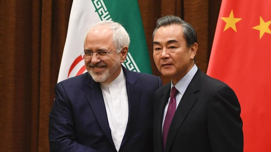 Iranian Foreign Minister Mohammad Javad Zarif, left, poses with Chinese Foreign Minister Wang Yi before a meeting in Beijing Monday, Dec. 5, 2016. (Greg Baker/Pool Photo via AP)