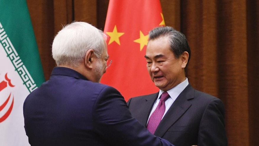 Iranian Foreign Minister Mohammad Javad Zarif, left, is greeted by Chinese Foreign Minister Wang Yi before a meeting in Beijing Monday, Dec. 5, 2016. (Greg Baker/Pool Photo via AP)