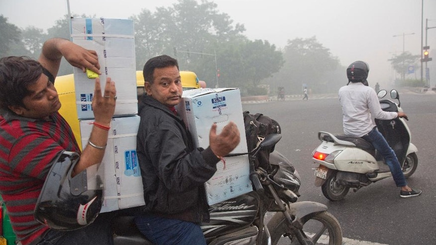 In this Sunday, Nov. 6, 2016 photo, people ride a motorcycle carrying air purifiers at a traffic intersection surrounded by a thick layer of smog in New Delhi, India. The news that the Indian capital is one of the dirtiest cities in the world, having surpassed Beijing for that dubious record, is three years old. But the awareness that it's toxic enough to leave its citizens chronically ill and requires long-term lifestyle changes is relatively nascent. (AP Photo/Manish Swarup)