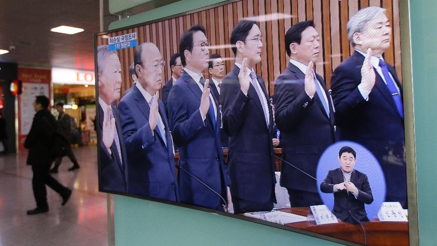 A TV screen shows from left, LG Group Chairman Koo Bon-moo, Hanhwa Group Chairman Kim Seung-youn, SK Group Chairman Chey Tae-won, Samsung Electronics Co. Vice Chairman Lee Jae-yong, Lotte Group Chairman Shin Dong-bin and Hanjin Group Chairman Cho Yang-ho take an oath during a hearing, at the Seoul Railway Station in Seoul, South Korea, Tuesday, Dec. 6, 2016. South Korea's most powerful business leaders from Samsung, Hyundai Motor and six other companies face grilling as lawmakers probe their links to a corruption scandal involving South Korea's president and her confidante. (AP Photo/Ahn Young-joon)