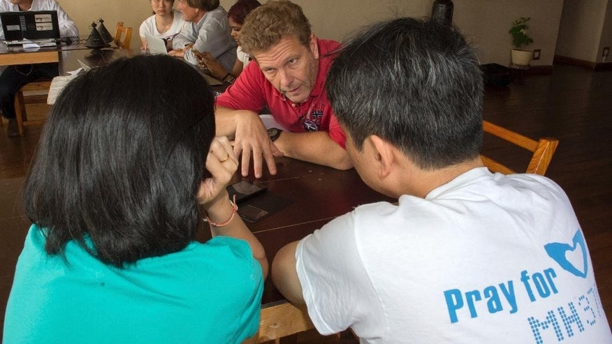 Ghislain Wattrelo, center, a French man whose wife and two of his three children were on a missing Malaysia plane, talks with other relatives of passengers during their meeting at a hotel in Antananarivo, Madagascar, Sunday, Dec. 4, 2016. The group of 8 relatives of some of the 239 people who were on a Malaysia Airlines plane that vanished in 2014 have arrived in Madagascar to ask for help in the search for debris from the missing aircraft that may have drifted across the Indian Ocean. (AP Photo/Alexander Joe)