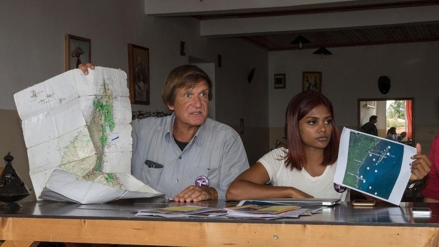 American wreckage hunter Blaine Gibson, left, and Grace Nathan, of Malaysia, one of the relatives of passengers of a missing Malaysia plane, look at photos and maps showing debris found in Madagascar, during their meeting at a hotel in Antananarivo, Madagascar, Sunday, Dec. 4, 2016. The group of 8 relatives of some of the 239 people who were on a Malaysia Airlines plane that vanished in 2014 have arrived in Madagascar to ask for help in the search for debris from the missing aircraft that may have drifted across the Indian Ocean. (AP Photo/Alexander Joe)