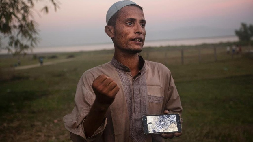 "In this Dec. 4, 2016 photo, Osman Gani, a Rohingya man from Myanmar, shows a video clip that he shot on his mobile phone as he describes the recent violence standing on the bank of the Naf River, near a camp for Rohingya people who illegally crossed the Myanmar-Bangladesh border in Teknaf, near Cox's Bazar, a southern coastal district about, 296 kilometers (183 miles) south of Dhaka, Bangladesh. The thin, fast-talking Arabic teacher, fled into nearby fields after his village was attacked on Nov. 11. As he fled north, he used his mobile phone to film destruction in other Rohingya villages he passed through. ""They came and killed mercilessly. They burned our homes,"" says Gani, standing near the Naf River over the weekend. ""No one was there to save us."" (AP Photo/A.M. Ahad)"