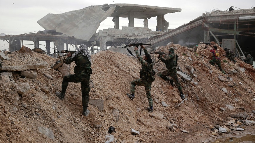 Syrian army soldiers fire their weapons during a battle with rebels at the Ramouseh front line, east of Aleppo, Syria, Monday, Dec. 5, 2016.