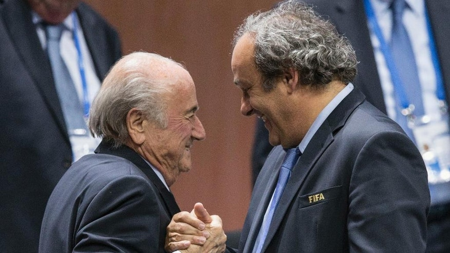 FILE - In this Friday, May 29, 2015 file photo, FIFA president Sepp Blatter is greeted by UEFA President Michel Platini, right, after Blatter's re-election as president at the Hallenstadion in Zurich, Switzerland. The Court of Arbitration for Sport is due to give its verdict Monday Dec. 5, 2016, on Blatter's appeal against a 6-year ban for approving a $2 million payment to Michel Platini in 2011. (Patrick B. Kraemer/Keystone via AP, File)