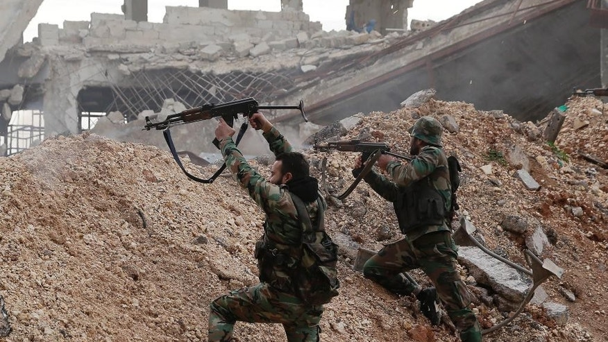 Syrian army soldiers fire their weapons during a battle with rebel fighters at the Ramouseh front line, east of Aleppo, Syria, Monday, Dec. 5, 2016. The government seized large swathes of the Aleppo enclave under rebel control since 2012 in the offensive that began last week. The fighting was most intense Monday near the dividing line between east and west Aleppo as government and allied troops push their way from the eastern flank, reaching within less than a kilometer (half a mile) from the citadel that anchors the center of the city. (AP Photo/Hassan Ammar)