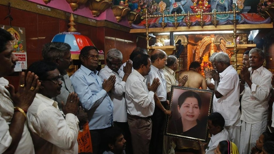 Supporters of Indian southern state of Tamil Nadu Chief Minister Jayalalithaa hold her photograph as they pray for her health at a temple in Mumbai, India, Monday, Dec. 5, 2016. Thousands of Jayalalitha supporters and well wishers across India prayed for her speedy recovery after she was readmitted to the hospital in Cheanni following a cardiac arrest on Sunday evening. (AP Photo/Rafiq Maqbool)
