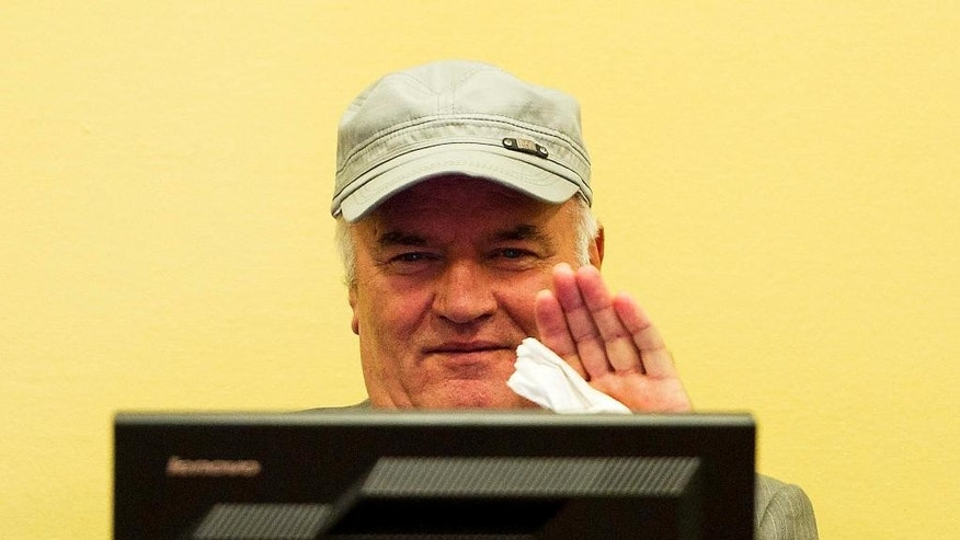 FILE - In this Friday, July 4, 2011, file photo former Bosnian Serb Gen. Ratko Mladic waves as he sits in the court room during his initial appearance at the U.N.'s Yugoslav war crimes tribunal in The Hague, Netherlands. UN prosecutors deliver their closing statement in the marathon genocide trial of former Bosnian Serb military chief Gen. Ratko Mladic, who is accused of commanding forces responsible for the worst atrocities of the Bosnian war. (AP Photo/ Valerie Kuypers, Pool, File)