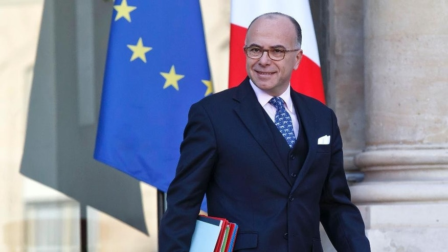 FILE - In this Wednesday, Dec. 23, 2015 file picture, French Interior Minister Bernard Cazeneuve leaves the Elysee Palace after the weekly cabinet meeting in Paris, France. French Prime Minister Manuel Valls has stepped down to focus on running for president in next year's election and has been replaced by Interior Minister Bernard Cazeneuve. (AP Photo/Michel Euler, File)